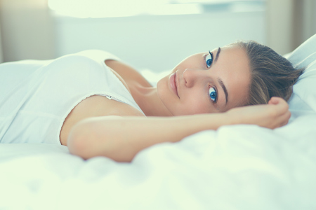 blissfully: Beautiful young woman lying in bed comfortably and blissfully