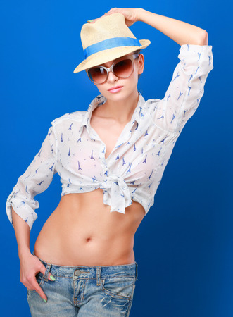 Portrait of pretty woman in sunglasses and hat over blue colorful background