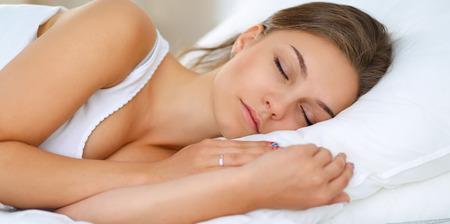 gente durmiendo: Hermosa mujer joven tendido en la cama cómodamente y felizmente