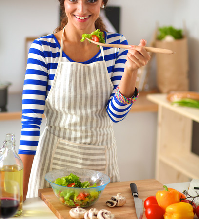 eating utensil: Young woman eating fresh salad in modern kitchen