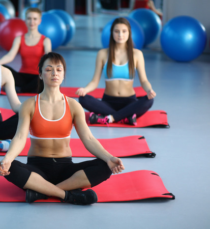 Sporty people sitting on exercise mats at a bright fitness studio Stock Photo
