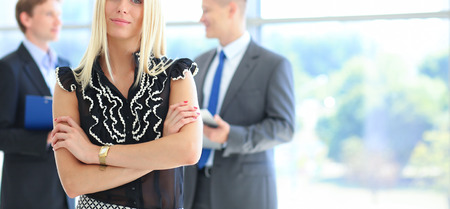 ambitious: Business woman standing in foreground in office