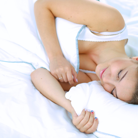 blissfully: A beautiful young woman lying in bed comfortably and blissfully