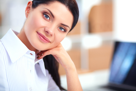 principal: Attractive businesswoman sitting on desk in the office