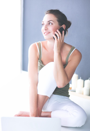 Attractive caucasian girl sitting on floor with phone Stock Photo