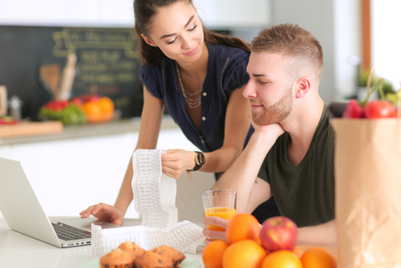 domicile: Couple paying their bills with laptop in kitchen at home