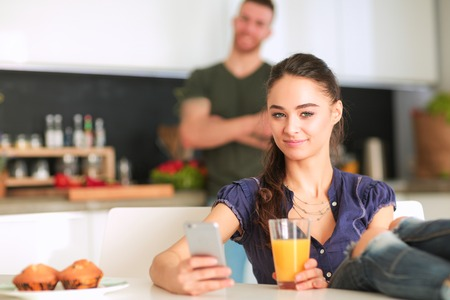 domicile: Happy couple using smartphone sitting in kitchen