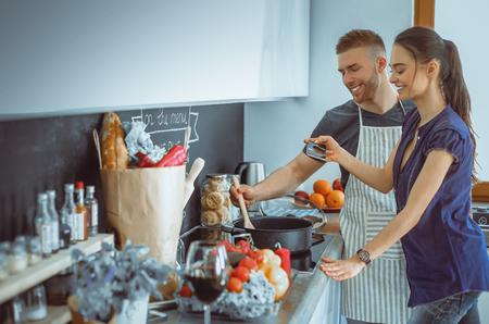 自宅のキッチンで料理をして一緒にカップル 写真素材