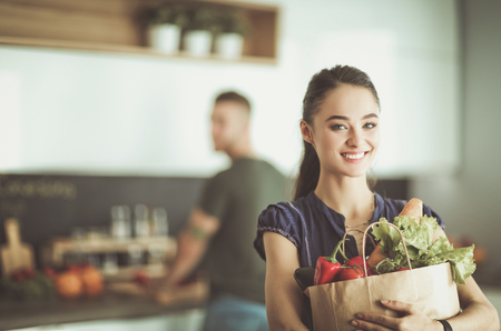 Young couple in the kitchen , woman with a bag of groceries shopping Imagens