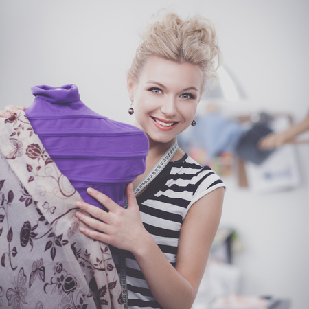 Smiling fashion designer standing near mannequin in office Stock Photo