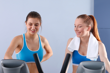 Group of people at the gym exercising on cross trainers Stock Photo