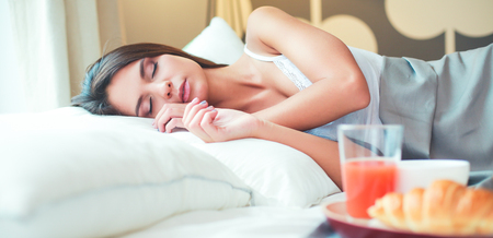 Young woman sitting in bed with a cup of milk Stock Photo