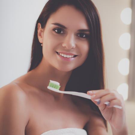 bathroom mirror: Portrait of a young girl cleaning her teeth Stock Photo