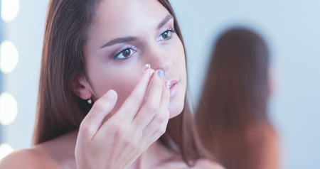 bathroom mirror: Attractive young woman applying cream on her Face