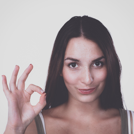 Happy young woman showing ok sign with fingers