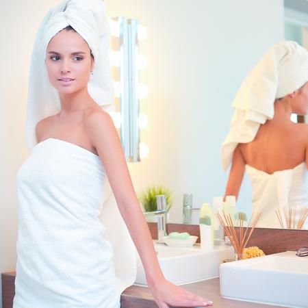 bathroom mirror: Young attractive woman standing in front of bathroom mirror