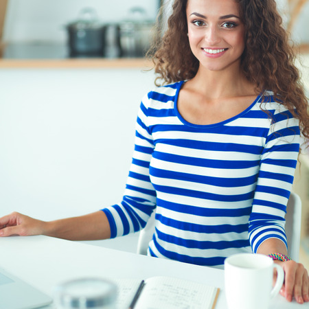 Smiling young woman with coffee cup and laptop in the kitchen at home Stock Photo