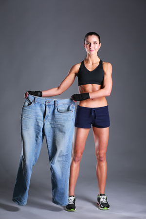 Young fitness woman showing that her old jeans