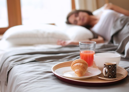 Breakfast in bed with coffee and croissant for attractive young woman