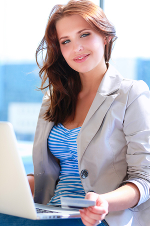 sell: Woman holding credit card on laptop for online shopping Stock Photo