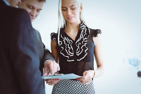 Business woman standing in foreground with a folder in her hands Stock Photo