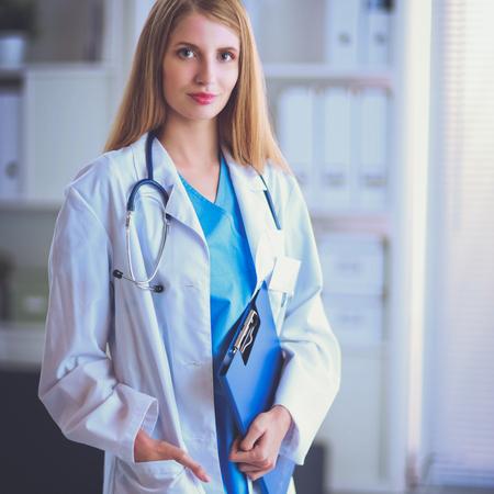 Doctor woman is standing in the near window