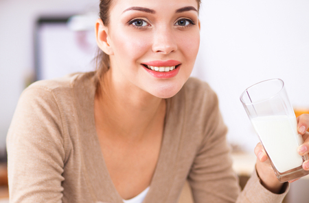 Happy young woman having healthy breakfast in kitchen Stock Photo