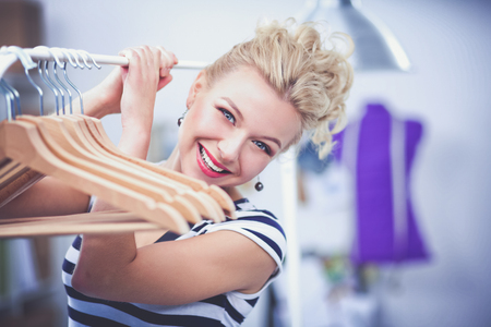 shopper: Beautiful young stylist near rack with hangers in office