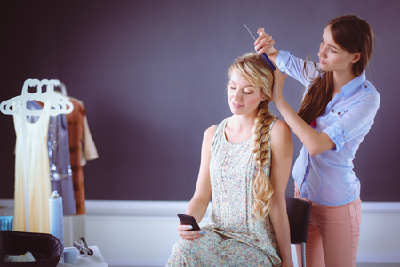 Young woman hairdresser do hairstyle girl in salon