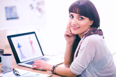 Portrait of attractive female fashion designer sitting at office desk