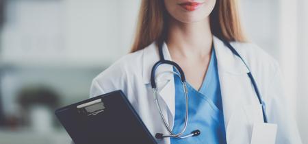 corridors: Portrait of woman doctor with folder at hospital corridor