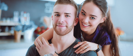 Beautiful young couple sitting in kitchen at home Stock Photo