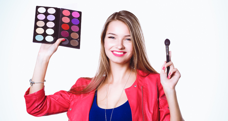 beautify: Young beautiful woman holds in one hand and a palette with paint and shadows for makeup, second hand brush for makeup