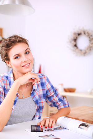 domicile: Portrait of young woman using mobile phone while having breakfast in kitchen at home Stock Photo