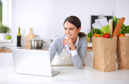 to spend: Smiling woman online shopping using computer and credit card in kitchen Stock Photo