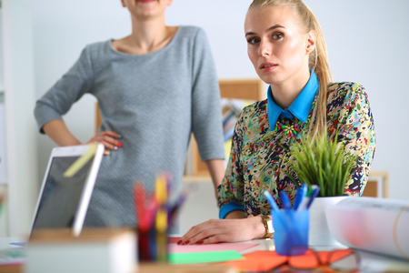 Young attractive female fashion designer working at office desk Stock Photo