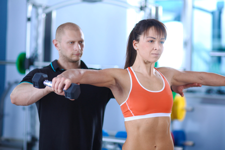 bodycare: Beautiful woman at the gym exercising with her trainer