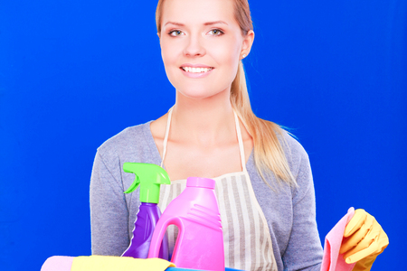 Cheerful woman is cleaning something with wisp and spray attentively. Stock Photo