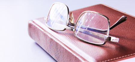 Modern eyeglasses on notebook paper on wood table