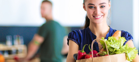 Young couple in the kitchen , woman with a bag of groceries shopping Stock Photo