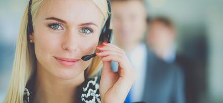 Onderneemster die met hoofdtelefoon bij camera in call centre glimlachen. Zakenlieden in hoofdtelefoons op achtergrond