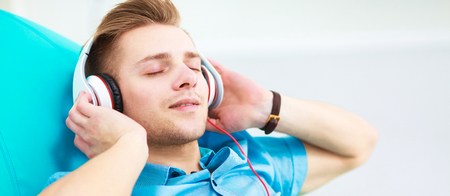 Man listening music with headphones at home