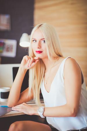 Fashion designers working in studio sitting on the desk.
