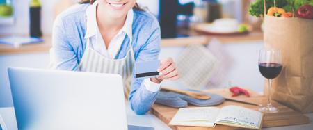 Lachende vrouw online winkelen met behulp van computer en credit card in keuken Stockfoto
