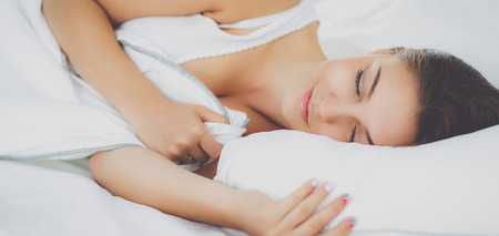 Beautiful young woman lying in bed comfortably and blissfully