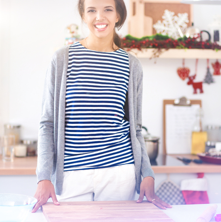 Young woman standing in her kitchen near desk Stock Photo