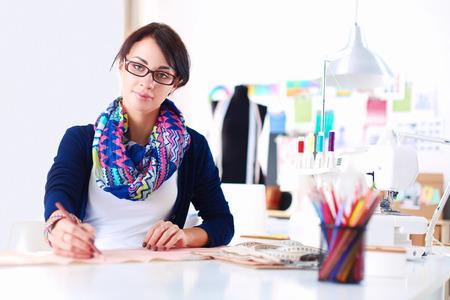 Beautiful fashion designer sitting at the desk in studio . Stock Photo