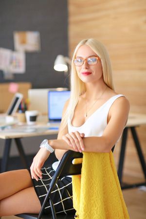 Portrait of an executive professional mature businesswoman sitting on office desk