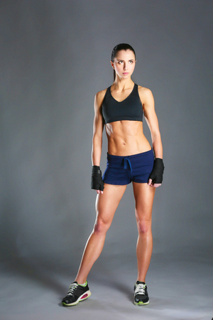 Muscular young woman posing in sportswear against black background. Stock Photo