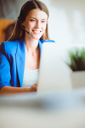 hotline: Portrait of beautiful business woman working at her desk with headset and laptop.